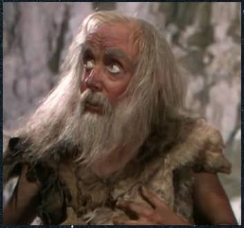 A photo of Ben Gunn from Treasure Island. He has a long grey bears and unkempt hair and wears raggedy clothes.